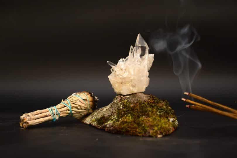 Imagem de incenso de palo santo queimando e ao lado dele alguns cristais para ajudar na limpeza.