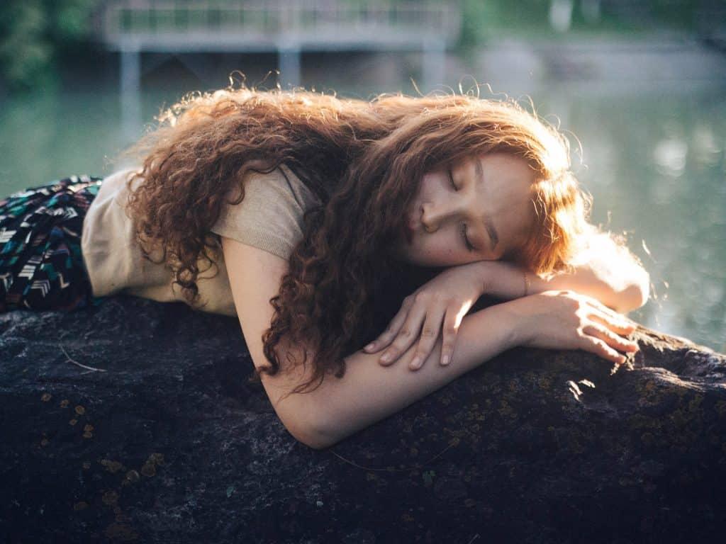 Mulher branca e ruiva deitada sobre uma pedra.