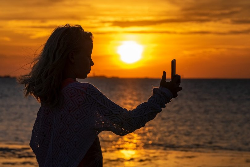Imagem da silhueta de uma jovem fazendo uma selfie em pleno por do sol em um alto dia de verão.