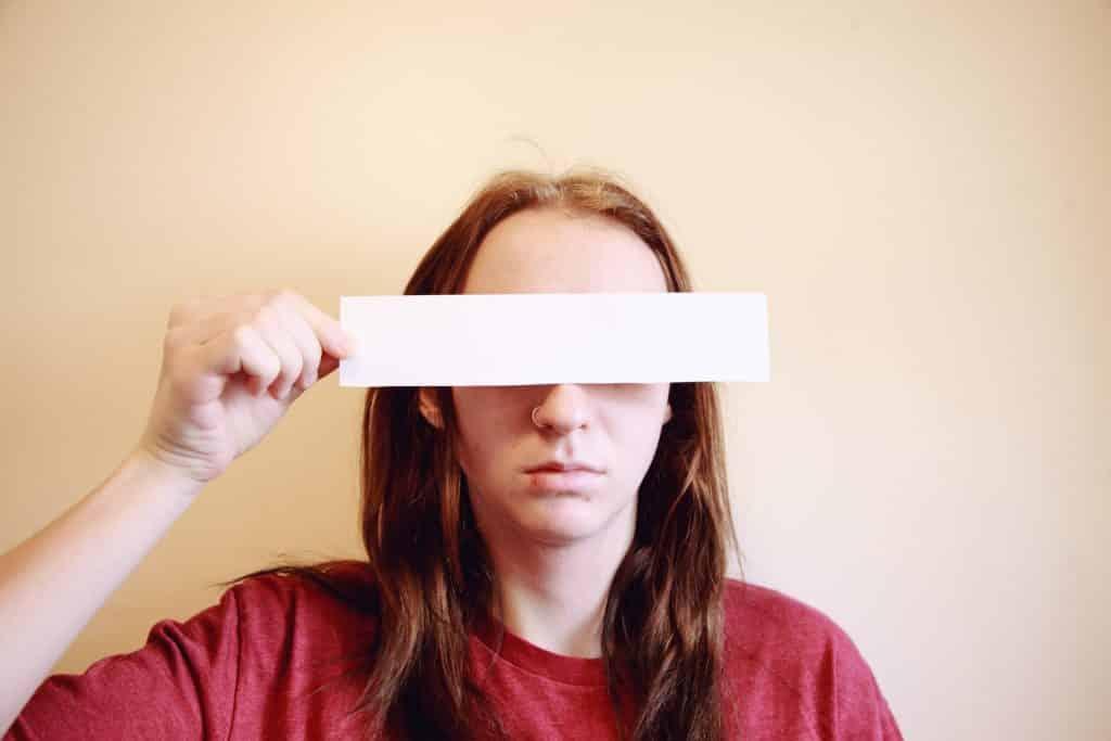 Mulher branca segurando pedaço de papel branco sobre os olhos.