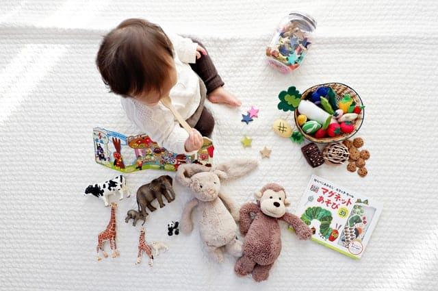 Bebê sentado com brinquedos espalhados à sua volta visto de cima