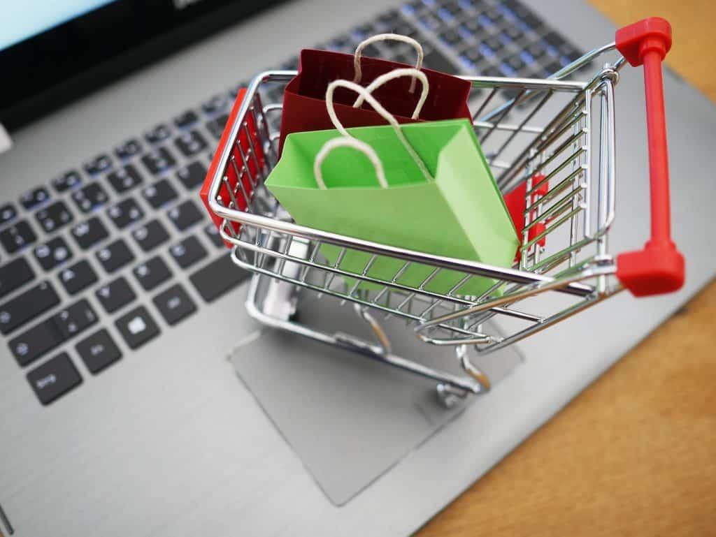 Imagem de um teclado de notebook e sobre ele uma miniatura de um carrinho de supermercado e dentro dele duas sacolas de compras vazias, sendo uma na cor verde e a outra na cor vermelha.