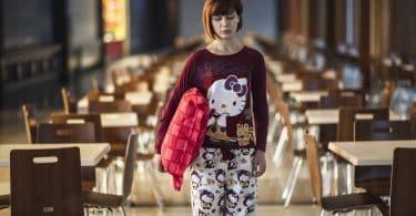 Imagem de uma mulher vestida com um pijama e segurando um travesseiro em um dos braços. Ela está caminhando dentro de um sala com muitas carteiras e cadeiras e está com insônia.