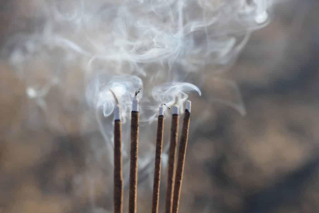 Imagem de 5 incenso de palo santo sendo queimados.