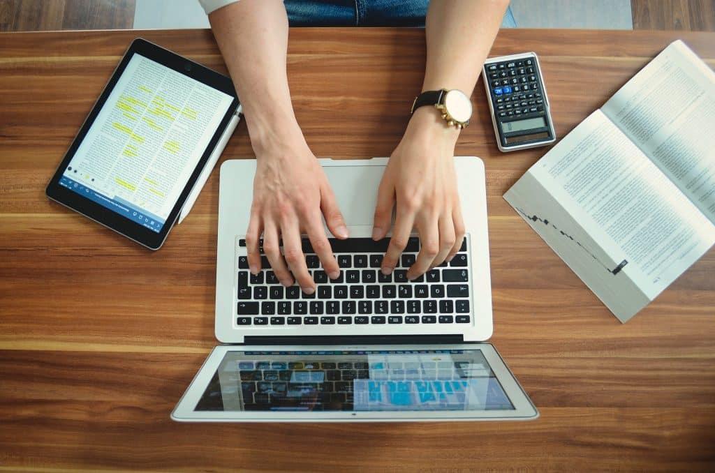 Imagem das mãos de um estudante sobre um notebook. Ele está estudando de forma remota devido à pandemia do novo coranavírus. Sobre a mesa temos um livro, uma calculadora e um ipad com caneta.