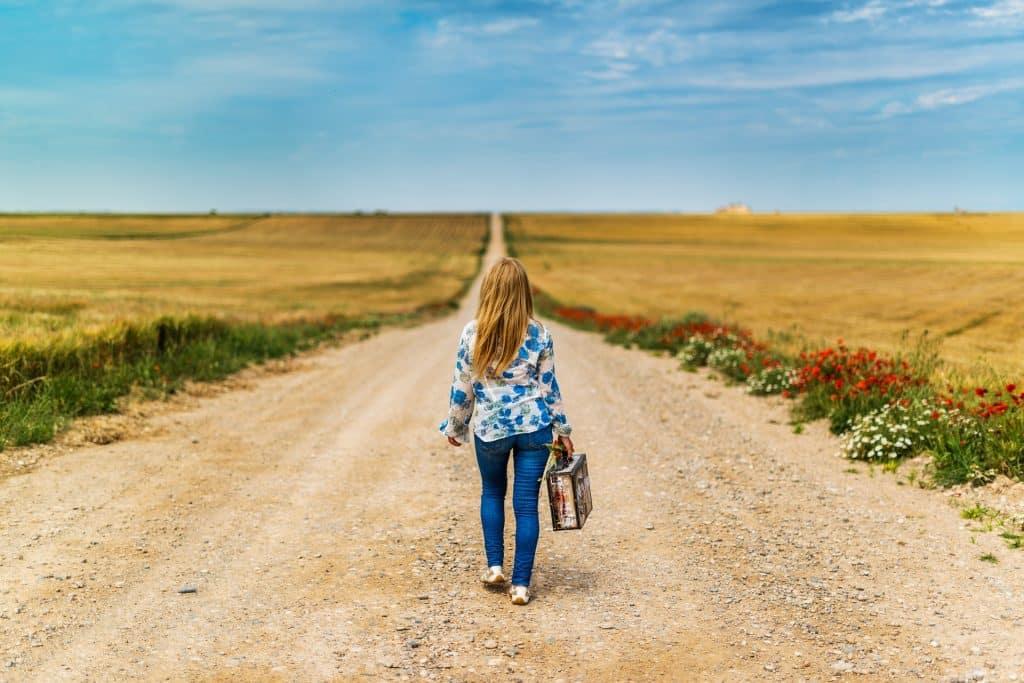 Imagem de uma extensa estrada de terra cercada por um campo verde. Nela, caminha uma mulher sozinha segurando em uma das mãos uma mala.