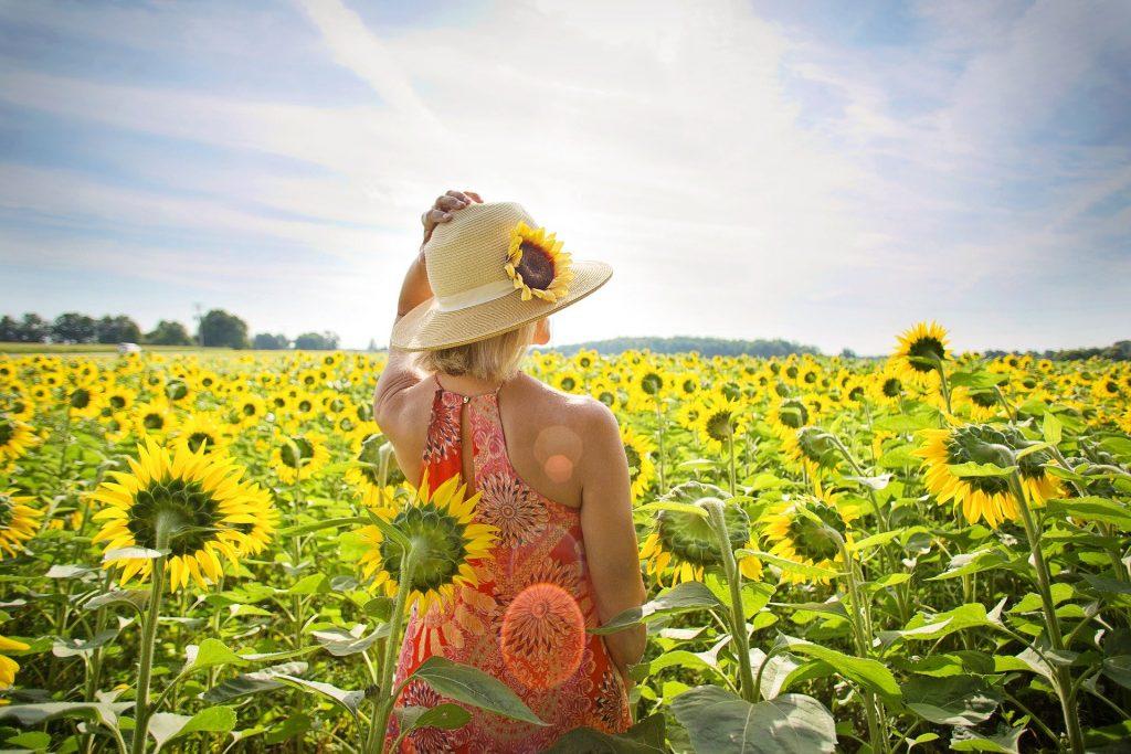 Imagem de um campo de girassóis e nele está uma mulher segurando um chapéu de palha sobre a sua cabeça. Ela está curtindo o verão aceitando a sua melhor forma.