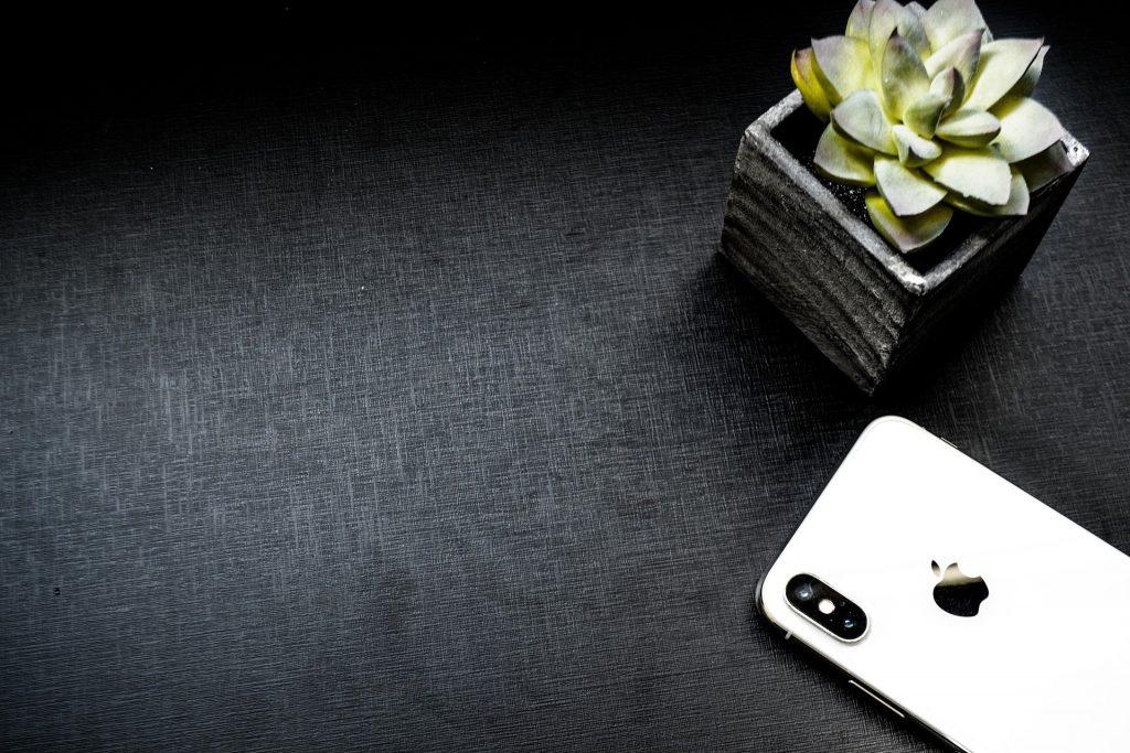 Imagem e um Iphone desligado sobre uma mesa de fundo preto. Ao lado dele um vaso e uma flor.