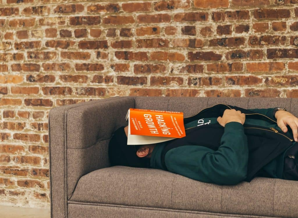Homem deitado em um sofá com um livro aberto sobre o seu rosto.