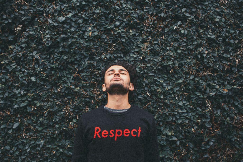 """Homem branco de barba preta, cabeça tombada para trás, usando moletom com a palavra """"respect"""" em vermelho, em frente à uma parede de folhas."""