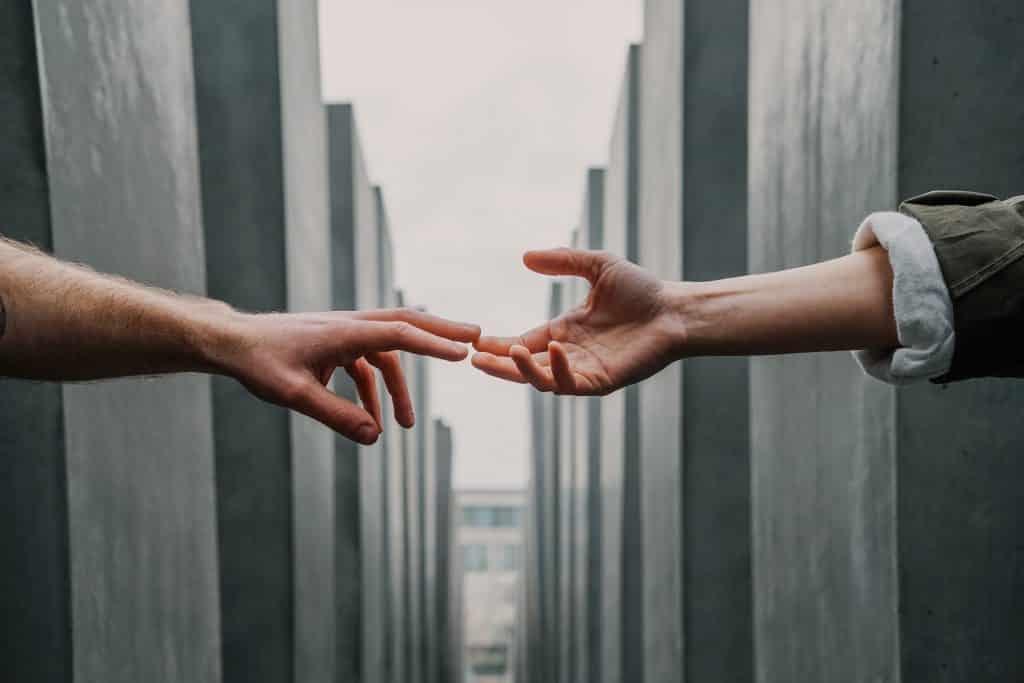 Duas pessoas encostando as mãos