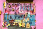 Imagem de um painel na cor rosa e nele está pendurado vários tipos de ferramentas para serem usadas para diversas ocasiões e preparos de materiais.