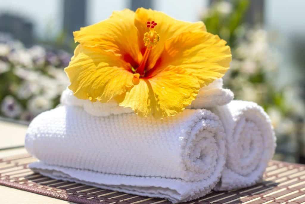 Imagem de duas toalhas brancas e de um flor de hibisco amarela sobre elas. Elas rementem as receitas de banho de assento para a candidíase.