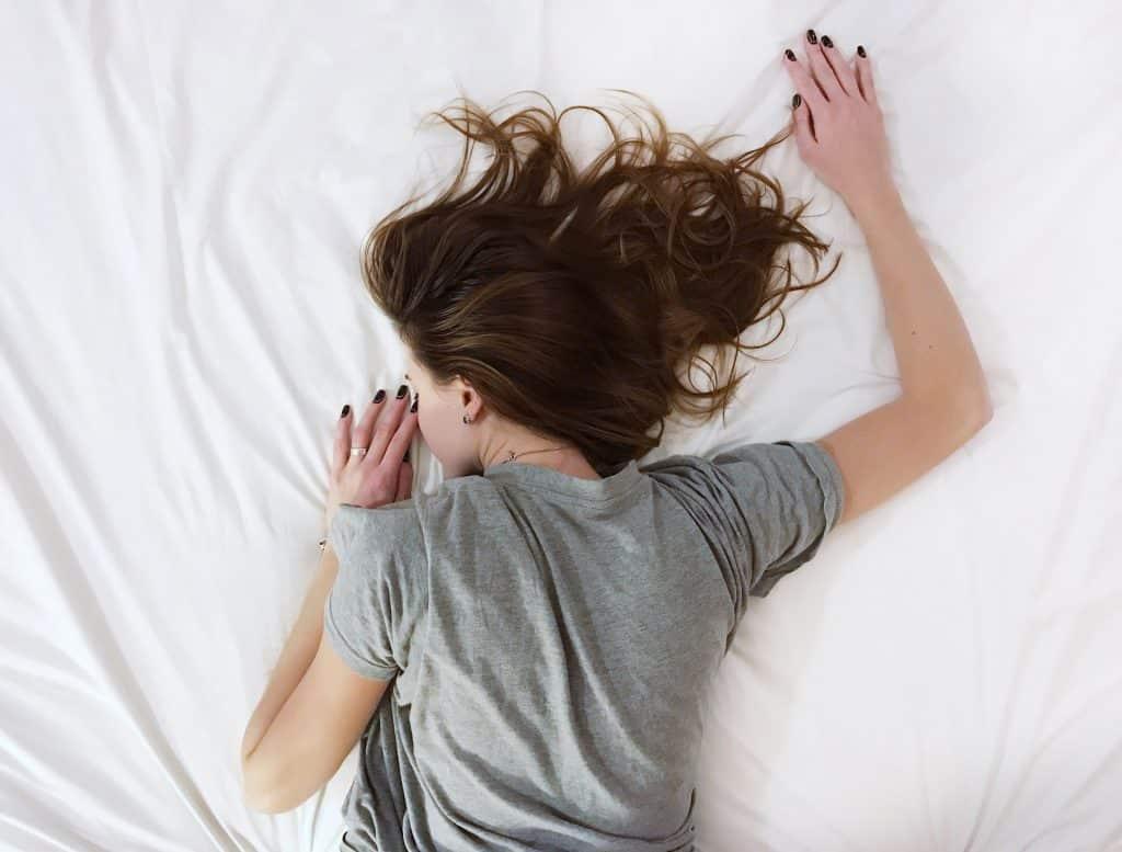 Mulher de costas deitada em uma cama com lençóis brancos.
