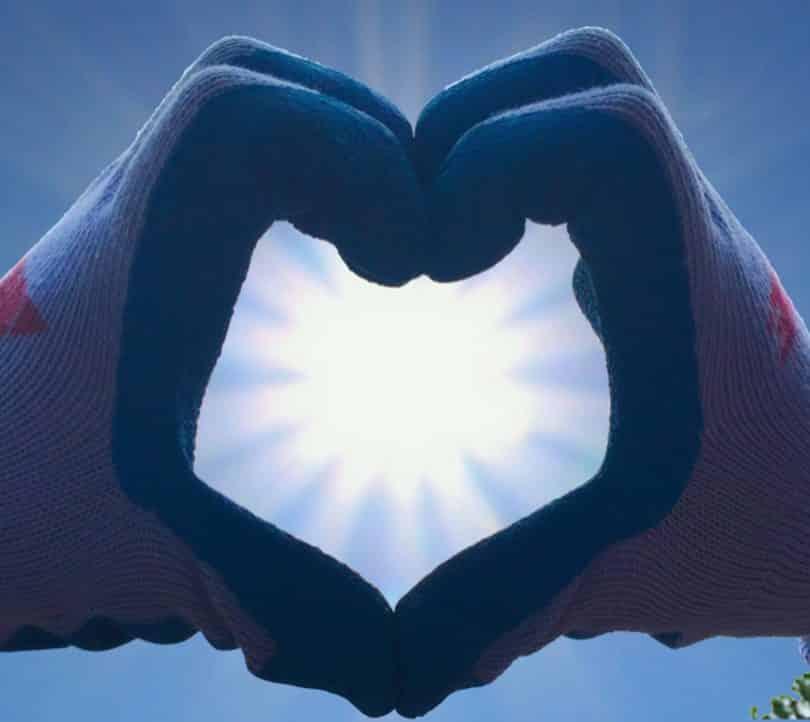 Imagem de uma mão com luvas em formato de coração representando o amor. Ao fundo a imagem de uma luz branca.