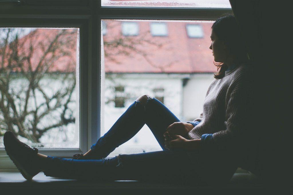 Mulher sentada de lado em uma janela olhando para a rua com semblante sério.