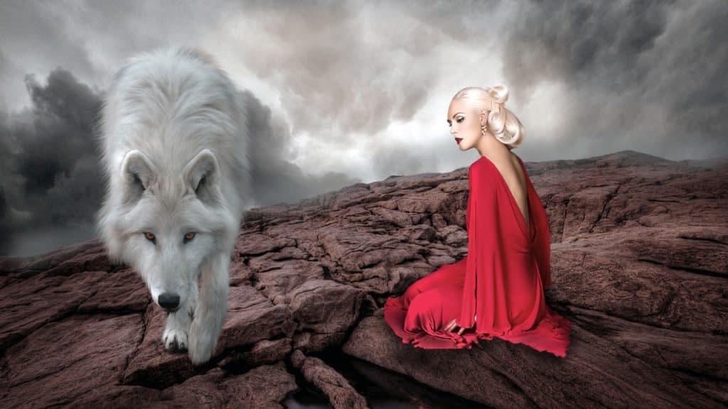 Imagem de um lobo branco e ao seu lado uma mulher loura usando um lindo vestido longo na cor vermelha. Eles estão em um terreno árido e seco.