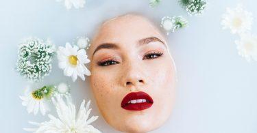 Imagem de um rosto oriental. Sobre ele algumas flores brancas, enfeitando. É uma modelo com pele branca, olhos pintados e boca com um lindo batom na cor vermelho.