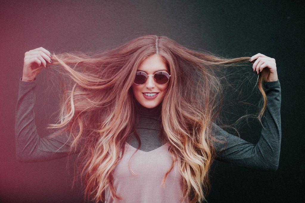 Imagem de uma mulher linda, de cabelos longos e ruivos. Ela segura as pontas dos seus cabelos e está usando um óculos de sol arredondado.