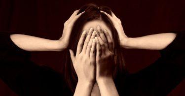 Imagem do rosto de uma mulher e sobre ele está suas mãos. Ela está indecisa ser quer mudar ou continuar na mesma situação.