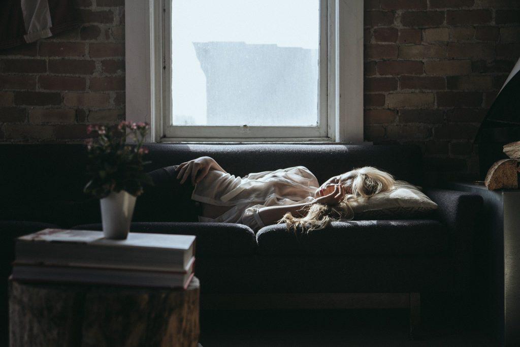 Imagem de uma mulher deitada e dormindo no sofá. Ela está cansada e aparentemente tendo um pesadelo.