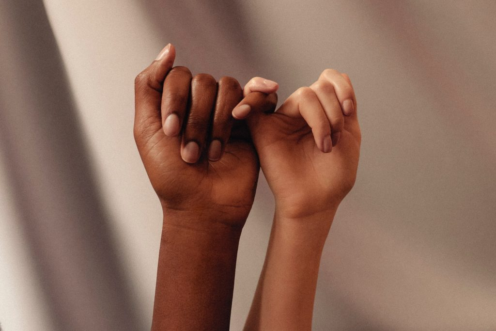 Dedos mindinhos, um branco, outro negro, se entrelaçando.
