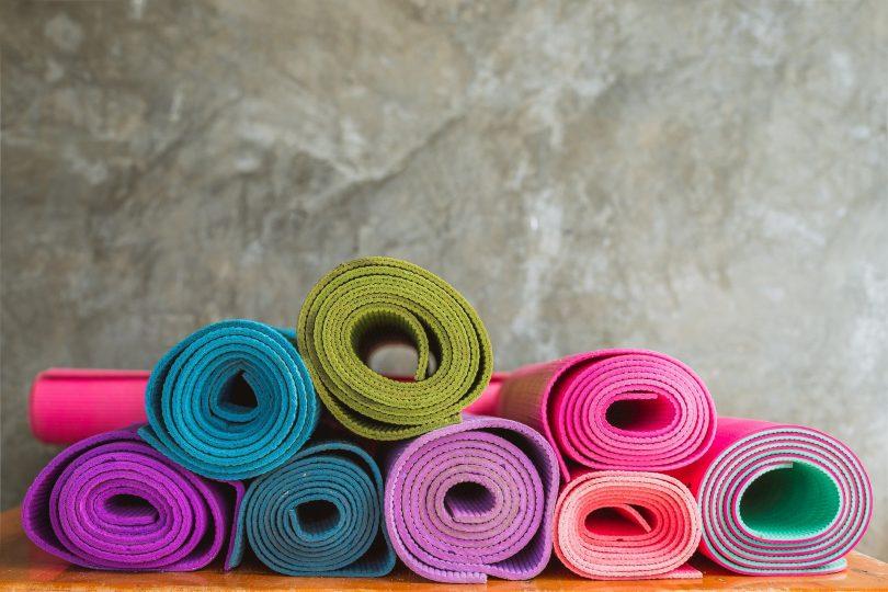 Imagem de diversos tapetes de yoga de várias cores. Eles estão enrolados dispostos sobre uma bancada.