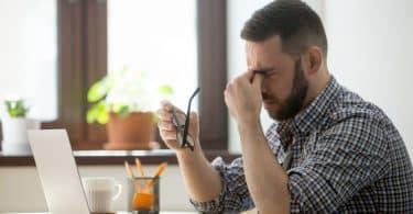 Homem sentado em mesa de trabalho com mão nos olhos e expressão de estress