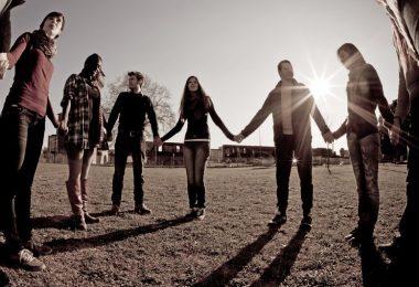 Roda de pessoas de mãos dadas com sol refletindo ao fundo