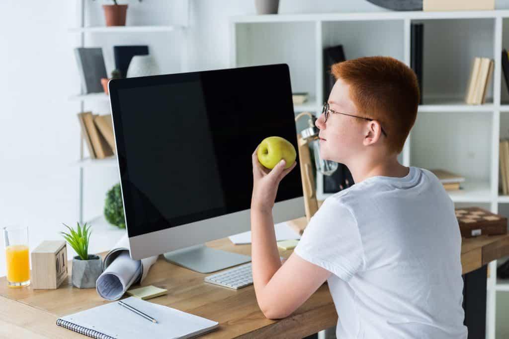 Imagem de um jovem garoto de cabelo curto e ruivo, vestindo uma camiseta básica na cor branca. Ele está sentado de frente para o seu computador e deu uma pausa nas redes sociais enquanto degusta uma linda e saborosa maçã verde.