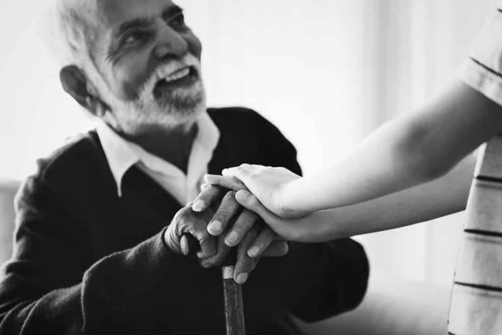 Imagem de um senhor idoso negro com barba branca. Ele está sentado, segurando em uma de suas mãos uma bengala. Sobre as mãos dele, as mãos de uma criança.