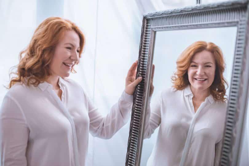 Mulher em frente ao espelho sorrindo