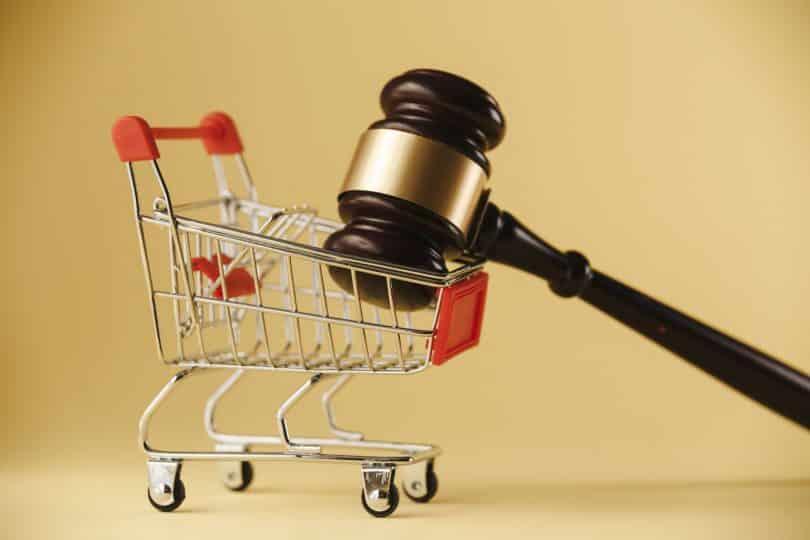 Carrinho de supermercado com martelo de juiz em cima.
