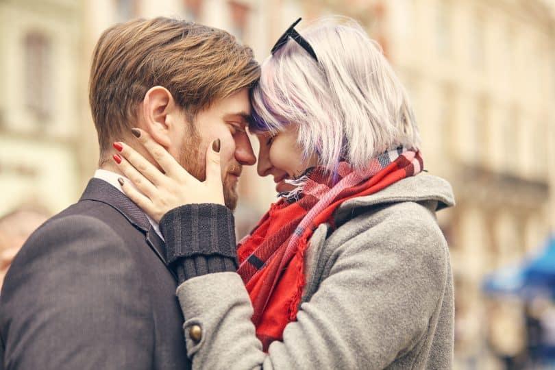 Homem e mulher brancos com cabeças encostadas, as mãos da mulher no rosto do homem.