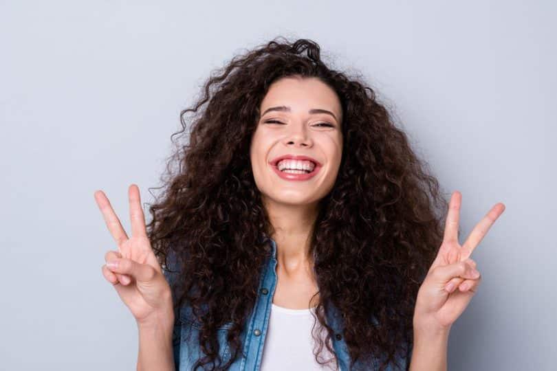 Mulher sorrindo fazendo sinal de paz e amor com as mãos