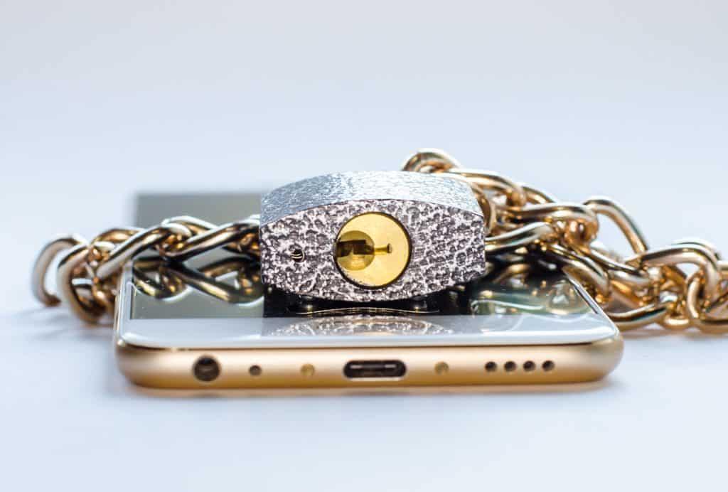 Imagem de um celular dourado envolto de uma corrente com cadeado. Ele está disposto sobre uma mesa branca.