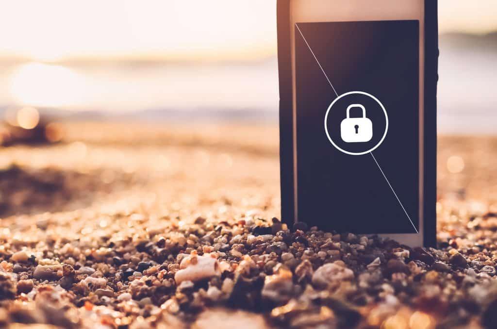 Imagem de um piso forrado com pequenas pedrinhas nas cores marrom, bege, branco e preto. Sobre elas um celular em pé, desligado e na tela dele aparece a imagem de um cadeado desenhado.