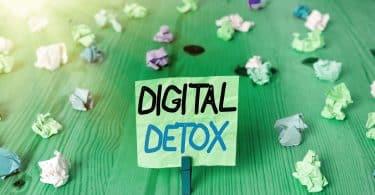 Imagem de uma mesa de madeira verde e sobre ela vários papeizinhos coloridos amassados e um post-it amarelo preso a um pregador. Nele está escrito a palavra em inglês: Detox Digital.