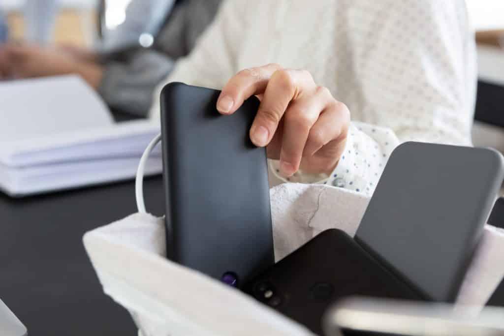 Imagem de uma mulher sentada à frente de um caderno. Ao lado dela uma outra pessoa e à frente um cesto com vários aparelhos celulares desligados.