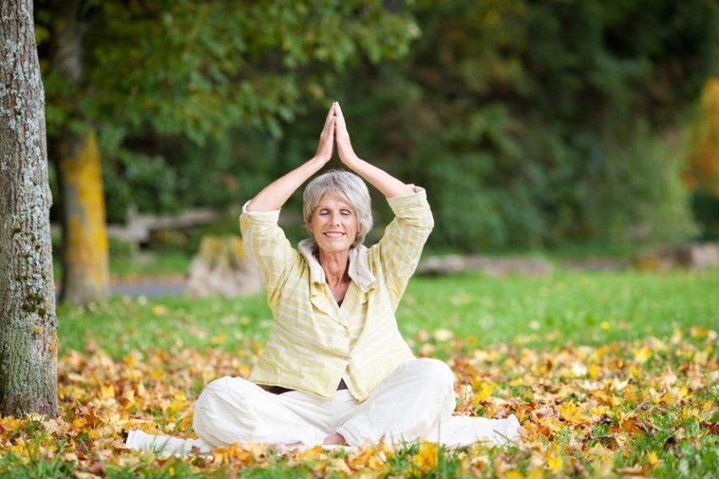 Mulher madura sentada em folhas secas meditando ded olhos fechados e sorrindo