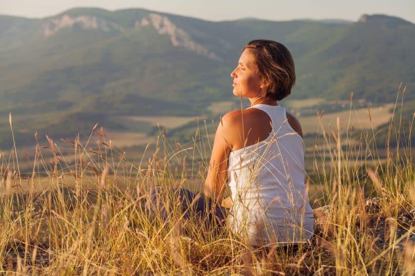 Mulher branca sentada num campo com os olhos fechados.