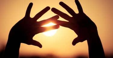 Silhueta de mãos no pôr-do-sol.