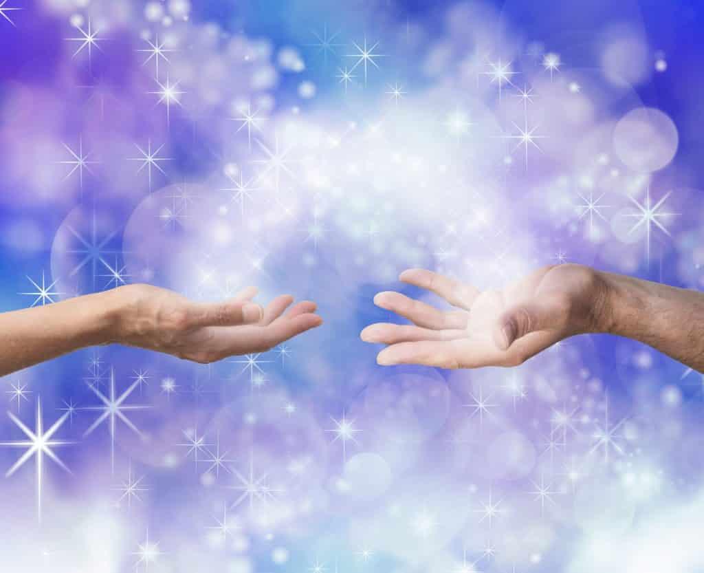 Mãos estendidas uma para a outra com uma luz roxa saindo por trás.