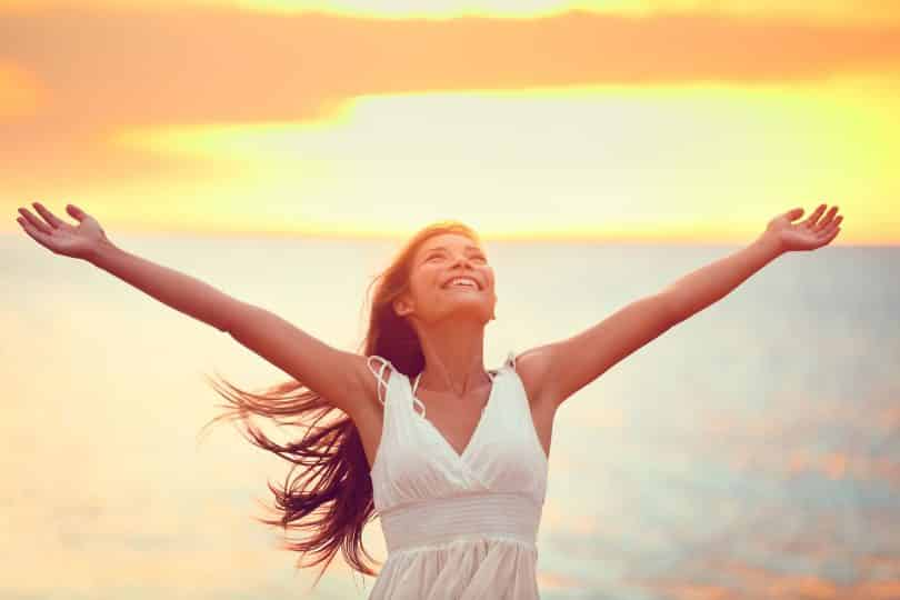 Mulher sorrindo com os braços levantados.