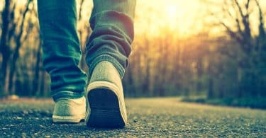 Pés de tênis andando em estrada com sol refletindo ao fundo