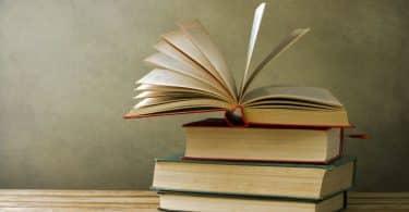 Livros em pilhados com um no topo aberto
