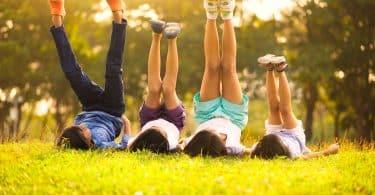 Crianças deitadas na grama com as pernas levantadas.