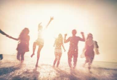 Silhueta de pessoas correndo na beira do mar.