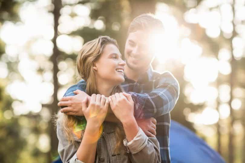 Casal abraçado sorrindo em fundo de árvores