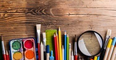 Lápis de cor, lupa e tintas em mesa de madeira